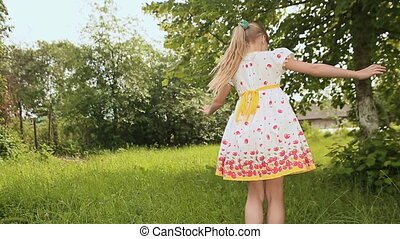 Girl in white dress is turned on sunny meadow.