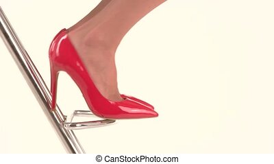 Feet in red heel shoes. Glossy footwear on heel. Bright and...