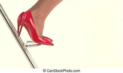 Feet in red heels. Glossy footwear on high heel. Look trendy...