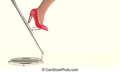 Feet in high heels. Bright red footwear. Attractive and...