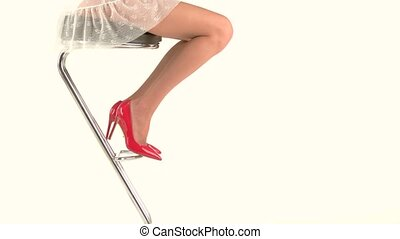 Legs in high heels. Female sitting on bar chair. Look...