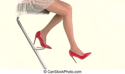 Legs wearing red heel shoes. Girl sits on bar chair. Look...
