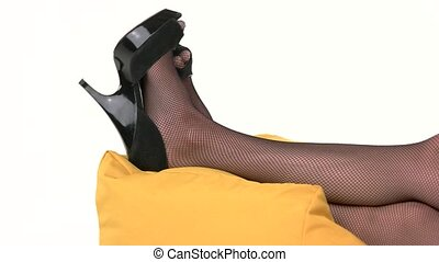 Feet in black heels. Legs lying on a pillow. Lay down for a...