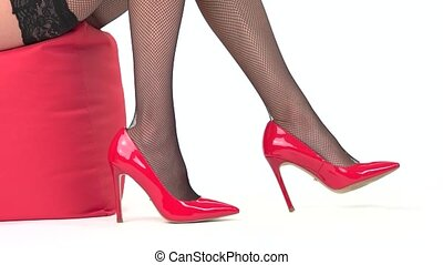 Female legs wearing red shoes. Heels and black fishnets. Get...