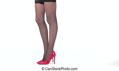 Isolated lady's legs in shoes. Black fishnets and red heels....
