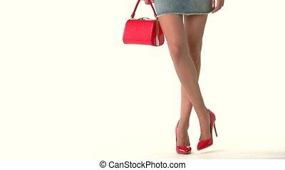 Legs wearing heels and purse. Short blue denim skirt....