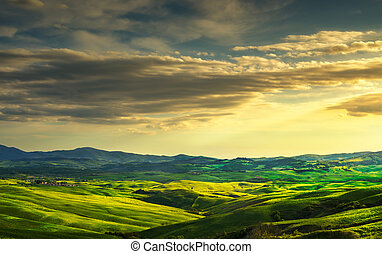 Tuscany spring, rolling hills and green fields on sunset. Rural landscape. Italy