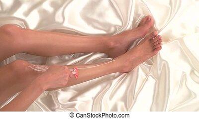 Female hand is shaving leg. Legs on white silk cloth. Make...