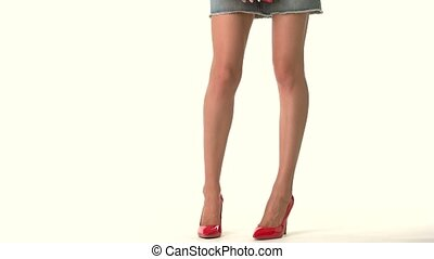 Legs in heels and handbag. Short blue jeans skirt. How to...