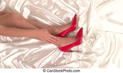 Woman touching her leg. Red shoes on high heel. Feel the...