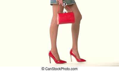 Handbag and legs of woman. Red shoes and bag. How to dress...