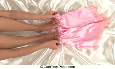 Legs of woman in bed.