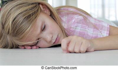 Portrait of sad little girl lying on floor at home at the...