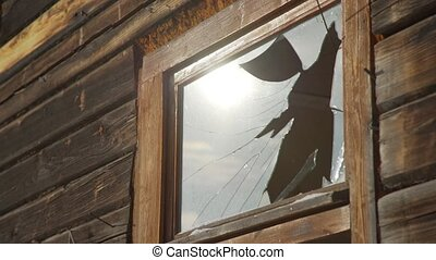 The demolition of the old house. Broken window of a shabby...