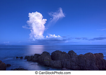 White thunderhead cloud over calm sea - Tall white...