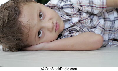 Portrait of sad little boy lying on floor at home at the day...