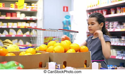 little girl at the store market chooses fruit orange -...