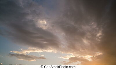 clouds moving rapidly across the sky during sunset, time...