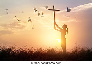 Woman praying with cross and flying bird in nature sunset...