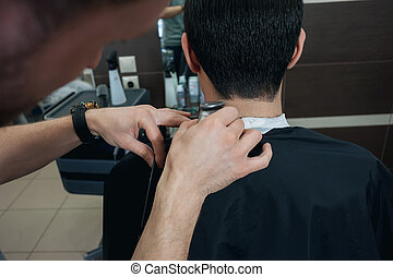 Master hairdresser cutting a short cut young man in barber...