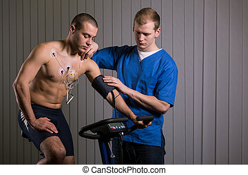 Patient with electrodes on chest - Doctor standing close to...