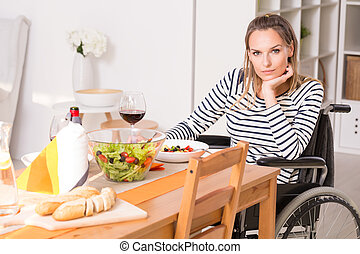 Women on wheelchair sitting at the table. - Pensive woman on...