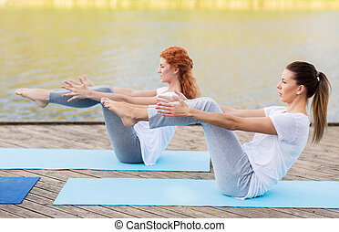 women making yoga in half-boat pose outdoors - fitness,...