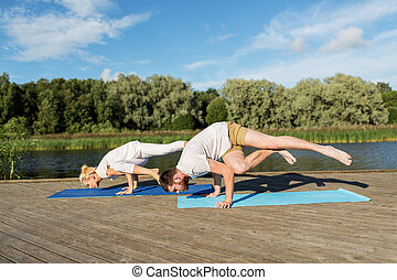 people making yoga exercises outdoors - fitness, sport and...