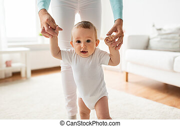 happy baby learning to walk with mother help