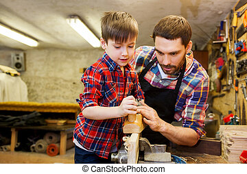 father and son with plane shaving wood at workshop - family,...