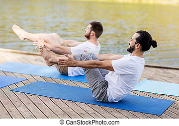 men making yoga in half-boat pose outdoors - fitness, sport,...