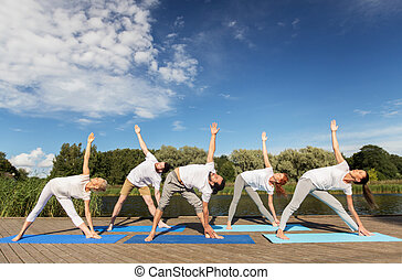 people making yoga in left triangle pose outdoors - fitness,...