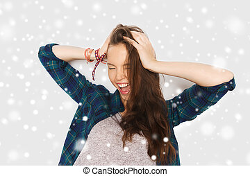 happy teenage girl holding to head over snow - winter,...