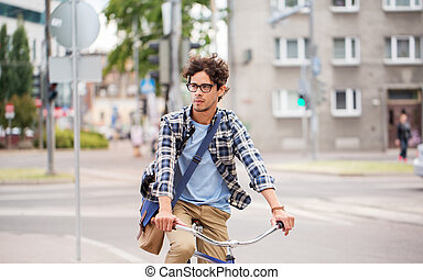 young hipster man with bag riding fixed gear bike - people,...