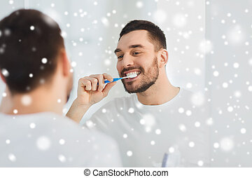 man with toothbrush cleaning teeth at bathroom - dental care...