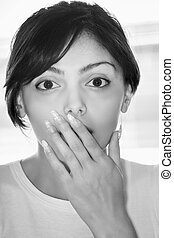 Portrait of surprized brunette woman covering mouth with...