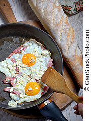 Fried eggs in a frying pan and homemade bread
