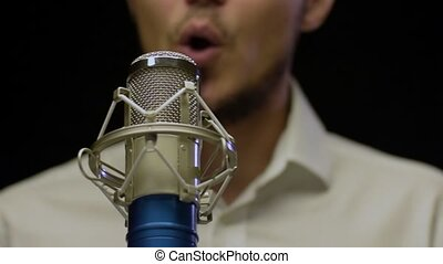 Young caucasian male singer performing at studio with...