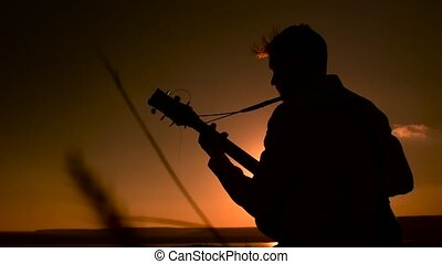Silhouette of young man sitting outdoors and playing acoustic guitar at sunset time