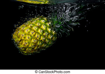 Pineapple falling in water on black background