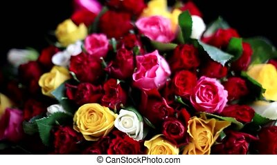 Bouquet of colorful roses on black background.