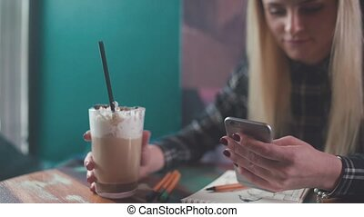 Stylish girl in a coffee shop, drink coffee, typing a sms -...