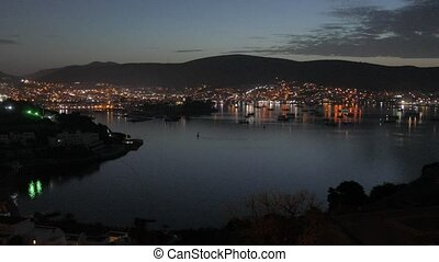 Night scenery of a coastal resort with lights on the hills and boats anchored in the bay. 4k