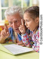 Grandfather and granddaughter with laptop