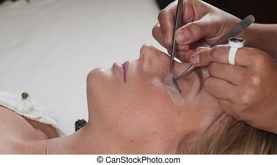 Woman Eye with Long Eyelashes. Eyelash Extension procedure.
