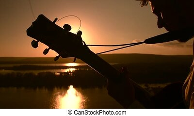 Young attractive male guitarist sitting and playing guitar outdoors at sunset time
