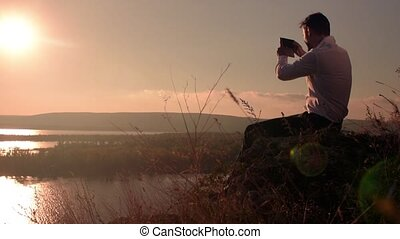 Young man sitting on the hill and taking panoramic picture with his smartphone