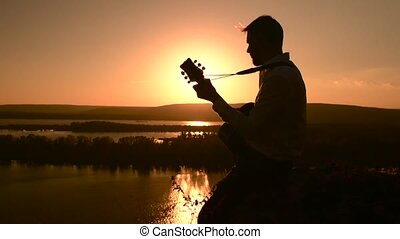 Young caucasian muician playing guitar outdoors at sunset...