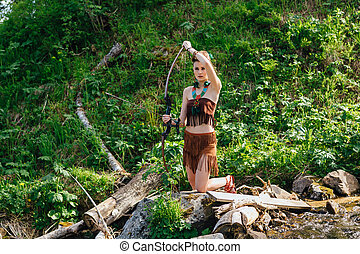 Young beautiful amazon girl hunting in the forest - The...