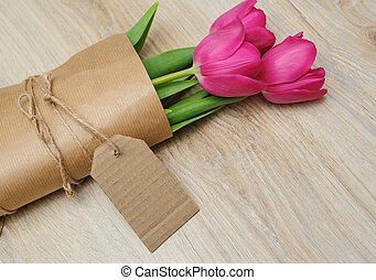 bouquet of red tulips in kraft paper.